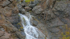 Close up of flow of small icelandic waterfall, water flows from rocks, white Stock Footage