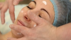 Cosmetologist cream face smears client Stock Footage