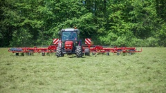 Tractor is preparing hay on a large field Stock Footage