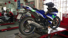 An unidentified service man repairs a motorcycle at a Yamaha service center. Stock Footage