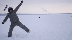 A young man makes a somersault in her arms, in the snow on the frozen lake, 4k Stock Footage