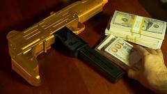 Narcolife gold gun money drug money Stock Footage