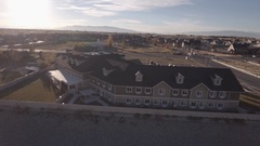 Aerial rotating shot of retirement home by the mountains in city Stock Footage