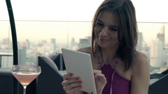 Young, happy woman using tablet computer on terrace in bar, super slow motion Stock Footage