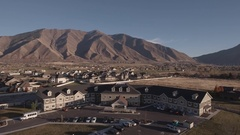 An aerial rising shot of retirement home by the mountains in city Stock Footage