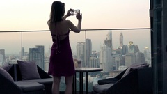 Elegant woman taking selfie photo with cellphone on terrace in bar  Stock Footage
