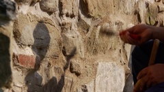 Workers who clean the plaster on the a wall of stone and brick, with a Stock Footage