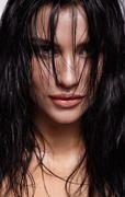 Portrait of a young brunette woman with shining wet make-up and shiny moist.. Stock Photos