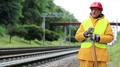 Railway man in red hard hat stands near railway track and looks at freight train HD Footage