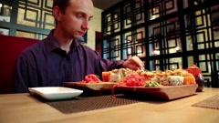 Man eats sushi in japanese restaurant Stock Footage