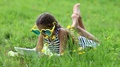 Girl in big sunglasses in the shape of hearts with tablet pc lies on green grass HD Footage