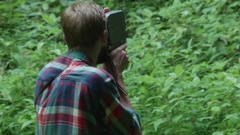 Tourist, filming with an old camera on film, the forest that is in fro Stock Footage