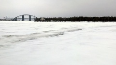 Pan from Dnipro river beach bank to Parkovyi Bridge on a cold winter afternoon Stock Footage