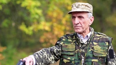 Retired officer in military uniform shoots a revolver Stock Footage
