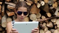 Girl in glasses near stack of firewood with tablet computer HD Footage