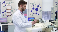 Man enters information from computer to the tablet at the laboratory Stock Footage