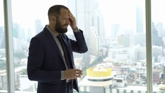 Businessman having head pain and drinking water by window in office Stock Footage