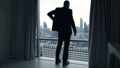 Young businessman unveil curtains and admire view from window at home Stock Footage