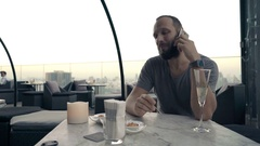 Young man talking on cellphone and eating snack on terrace in bar Stock Footage