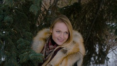 Beautiful young model participating in a photo shoot in the woods in winter. She Stock Footage
