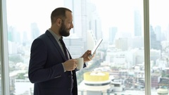 Young businessman reading news on tablet computer and drinking coffee by window  Stock Footage