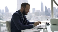 Young businessman with laptop thinking and having great idea in office  Arkistovideo