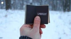 Lettering Wanderlust., Travel concept. Traveler holds a book in his hand with Stock Footage