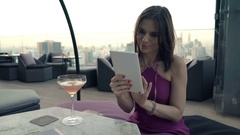 Young, happy woman using tablet computer and drinking cocktail in rooftop bar Stock Footage