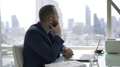 Businessman with laptop thinking and trying to solve problems in office  Arkistovideo