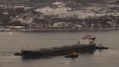 Kola Bay - three tugs pushing large ship in the winter. Stock Footage
