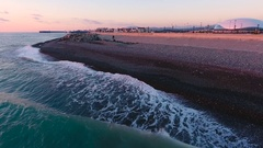 Aerial View. Flying above the sandy beach stone sea at sunset. Stock Footage