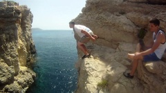 POV of a young man jumping off a cliff and doing a backflip in Malta. Stock Footage