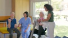 Multi racial nurses helping elderly couple in hospital gym Stock Footage