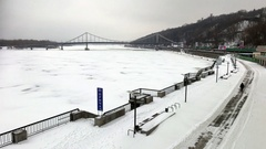 Frozen Dnipro river with Podil embankment and Parkovyi Bridge Stock Footage