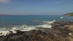 Tropical Beach Le Perouse, Maui Fly Over Lava Rocks & Ocean Towards Molokini Stock Footage