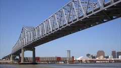 Pan from underside of bridge to New Orleans Louisiana skyline with mississippi r Stock Footage