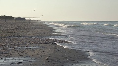 In far is man on morning beach with small waves on sea Stock Footage