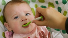 Baby eats first meals with fruit. Stock Footage