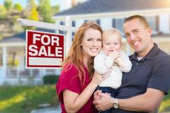 Young Military Family in Front of For Sale Sign and House Stock Photos