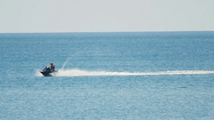 Man on jetski rides on ocean surface and filming Stock Footage