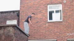 A young man doing a parkour freerunning jumping and flipping stunt. Stock Footage