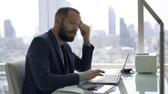 Young businessman having head pain while working on laptop in office Stock Footage