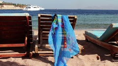 Wooden chair at the beach of background of blue sea and white yacht floats Stock Footage