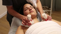 Herbal compressing balls massage Stock Footage