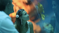 Girl and boy watching fish in an aquarium Stock Footage