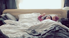 Cute little girl stretching her arms happily with a smile from waking up in her Stock Footage