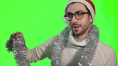 Handsome young man in stylish glasses and a hat of Santa Claus winds tinsel Stock Footage