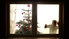 Funny child looking anxious on window waiting for Santa Claus  Stock Footage