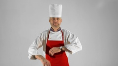 Handsome adult chef turns, he crosses his arms and nods his head on a gray Stock Footage