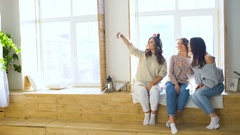 Three beautiful girls shoot selfie while sitting on window. Girlfriends having Stock Footage